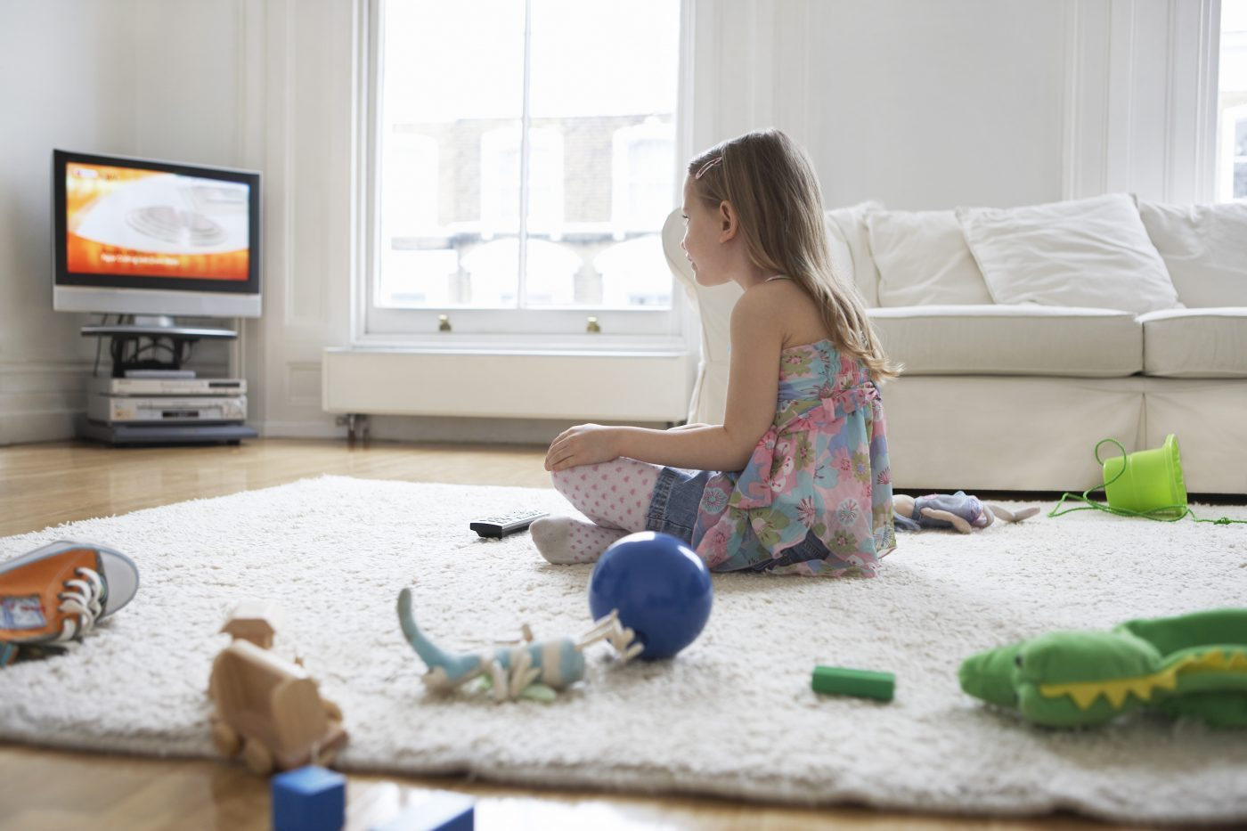Girl watching television in the living room.
