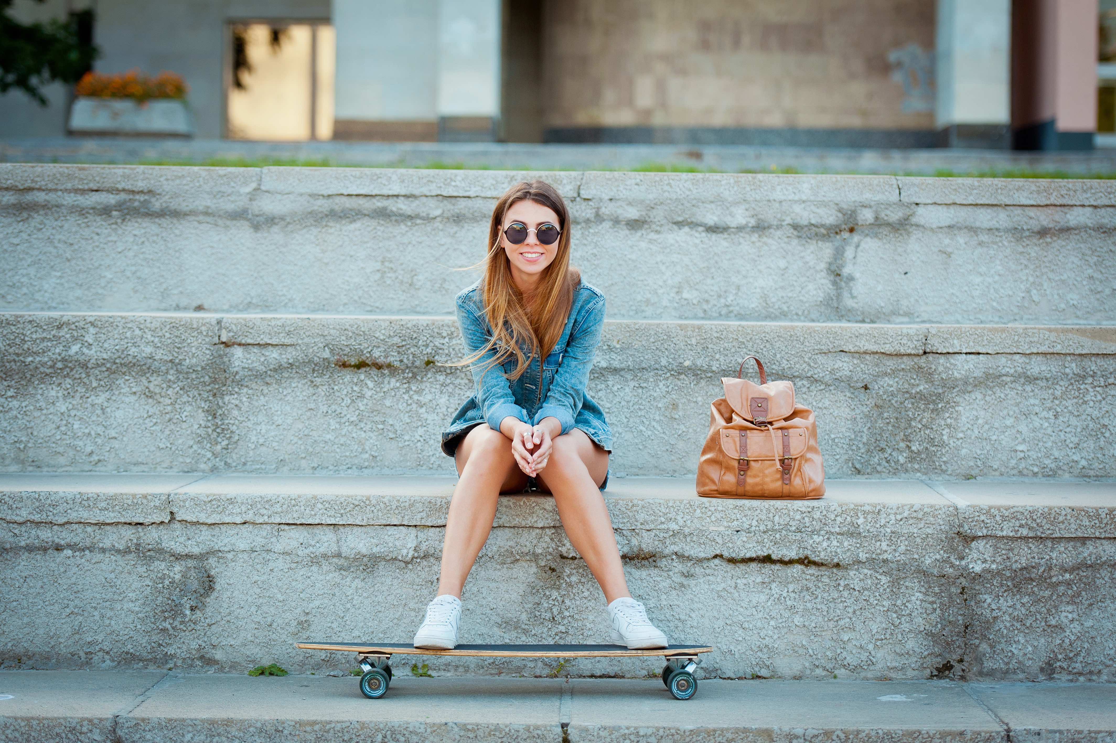 Girl sitting on the stairs with her skateboard.