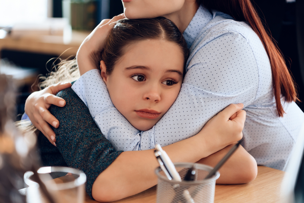Young sad mother hugs little upset daughter sitting in lawyer's office for divorce. Two parents fighting over child in divorce concept