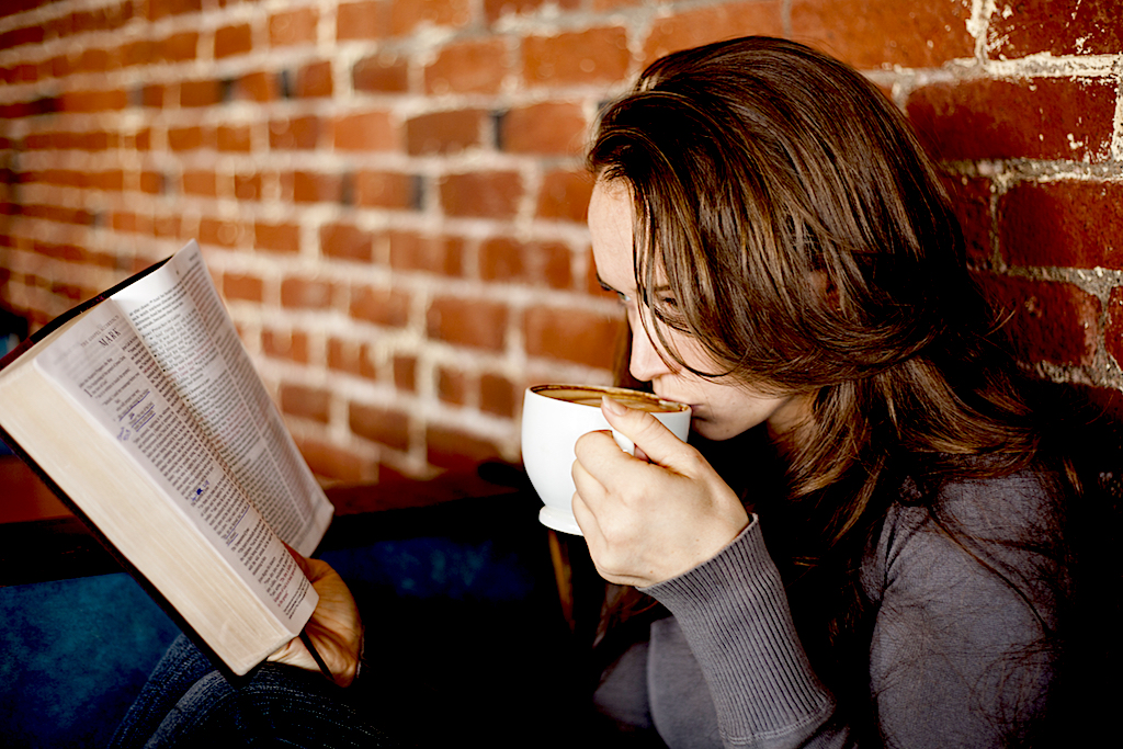 Portrait of a young woman with a white coffee cup reading the book of Mark in the Bible