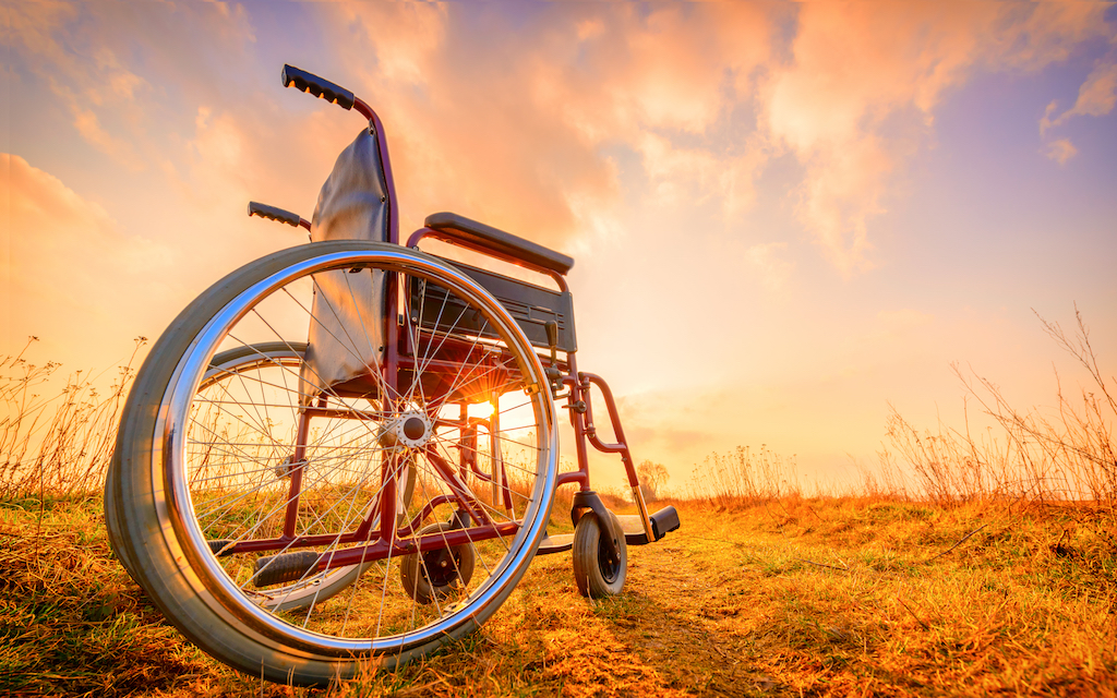 Empty wheelchair on the meadow at sunset. Miracle concept.