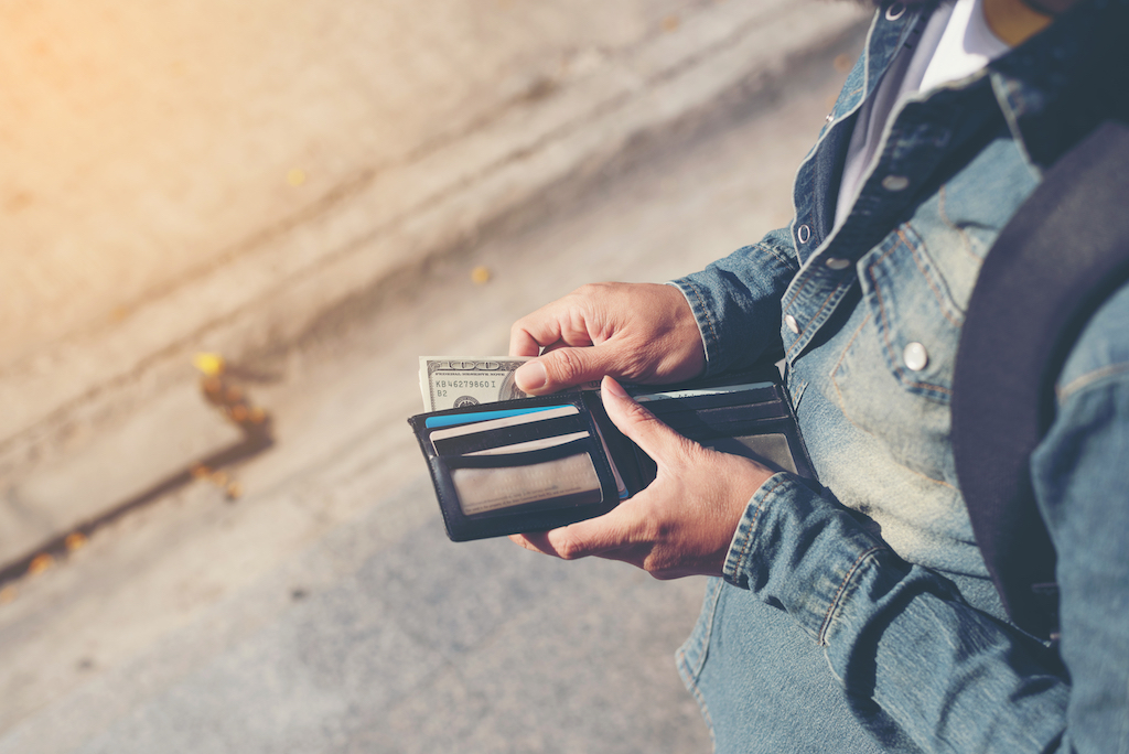 man hands holding wallet with credit cards and stack of money