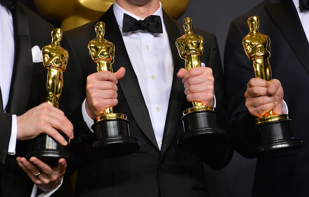 Oscar winners holding their awards in the photo room
