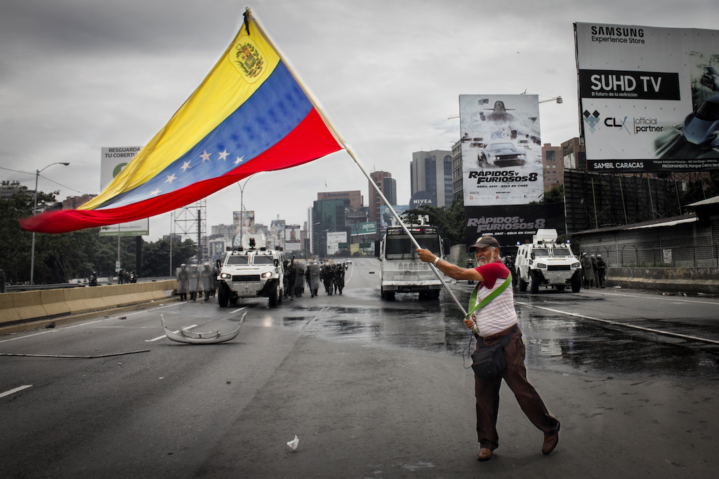 Protest in Caracas, Venezuela. Deputy of the National Assembly holds a Venezuelan flag when the protest is repressed by the Bolivarian National Guard with tear gas