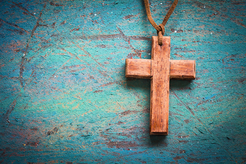 Image of wooden cross on blue retro background