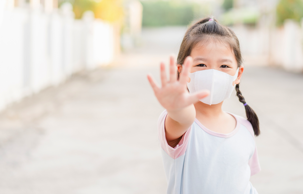 Coronavirus and Air pollution pm2.5 concept.Little chinese girl wearing mask for protect pm2.5 and show stop hands gesture for stop corona virus outbreak
