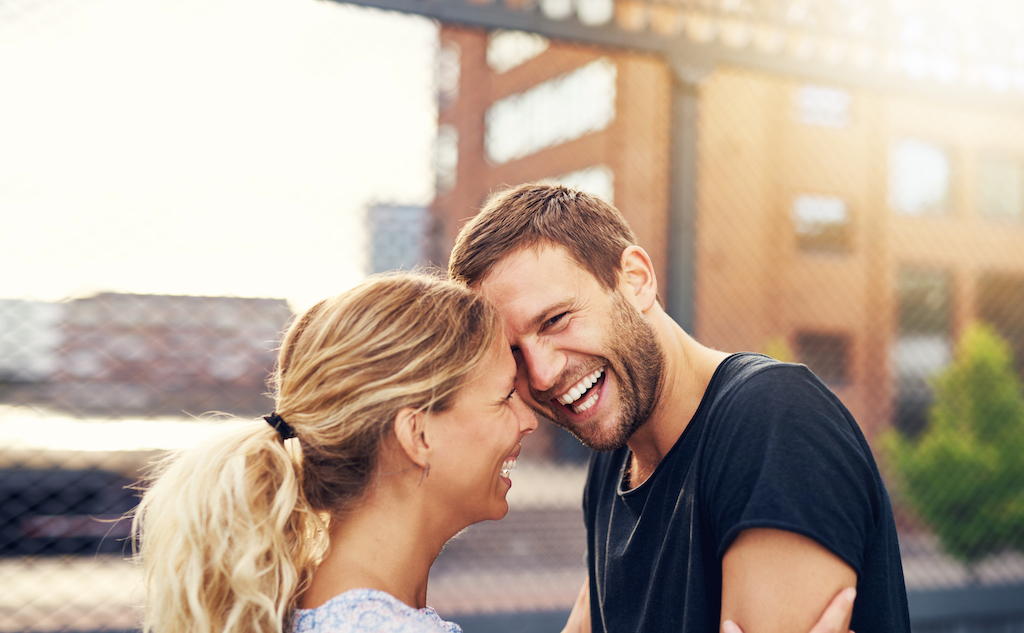 Happy spontaneous attractive young couple share a good joke laughing uproariously and hugging each other outdoors in an urban environment
