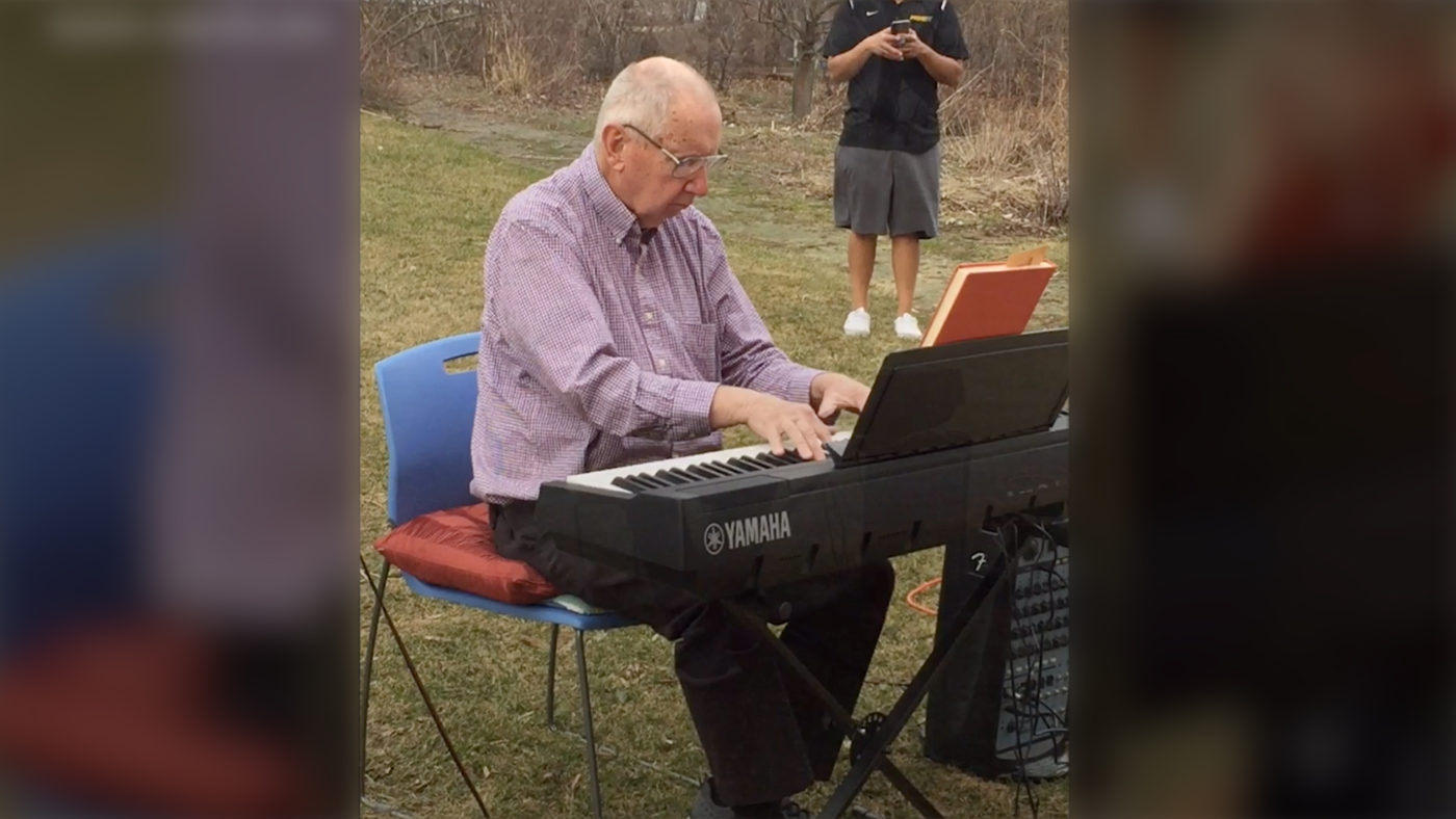 Man sitting at his piano playing outside