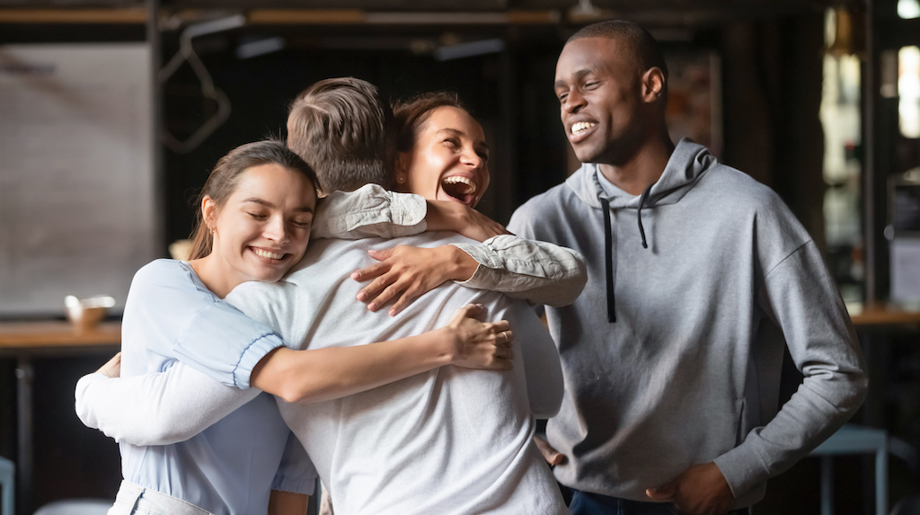 Excited diverse friends embrace greeting male buddy coming at meeting in cafe