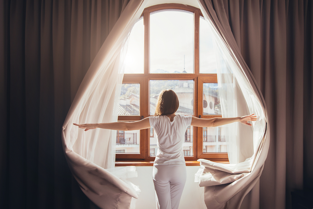 Rear view - young fit woman in home clothes opens curtains of bedroom window. Young girl is ready for new plans and new challenges. Concept of opening yourself to world, new affairs and new promises