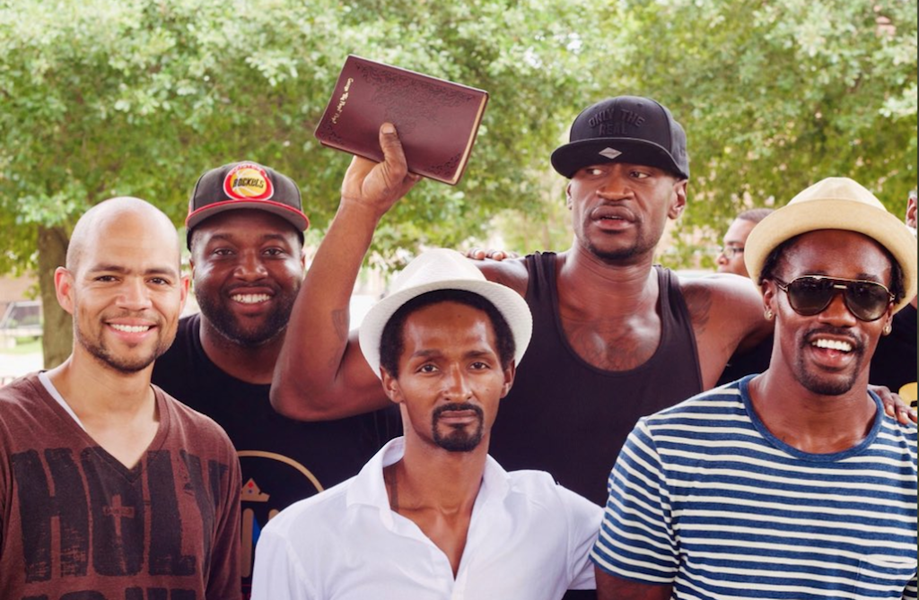 George Floyd with a group of men holding up Bible