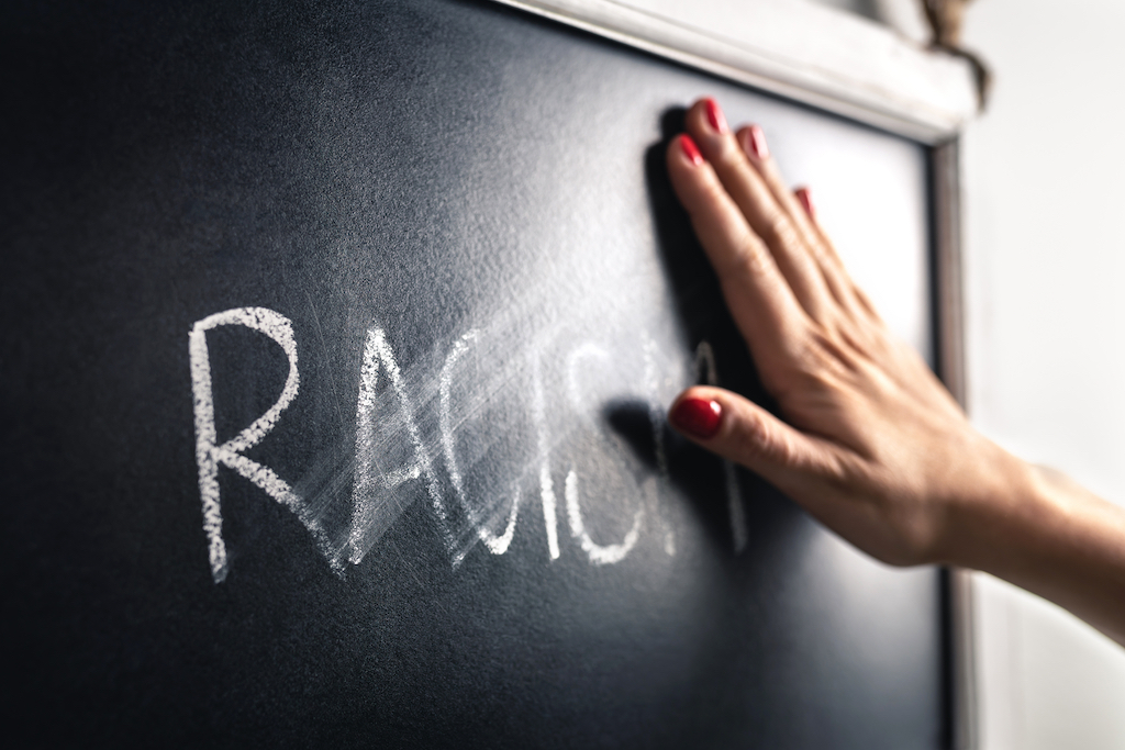 Racism concept. Stop hate and discrimination. Against prejudice and violence. Hand wiping off and erasing the word from blackboard